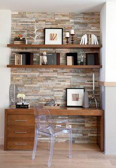 ladrillo visto, escritorio de madera con silla transparente, pared de piedra decorativa y estantes con libros