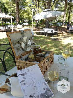 Hoogtepunt van een rondje langs de wijngebieden - en daarom ook razend populair - zijn de picknicks. Bij een landgoed als Boschendal boek je je 'Picque-Nique' (ver) vooruit om je plekje in de hangmat of de zitzak op het grote grasveld veilig te stellen. Als we plaatsnemen aan de witgedekte tafels met verwachtingsvolle lege wijnglazen, komt een ober onze picknickmand met begeleidend A4'tje brengen. 'A Sunny Afternoon' heet ons menu . Photo: picknickmand, Boschendal, Franschhoek, Zuid-Afrika South Africa, Restaurant Ideas, Afrikaans, Table Decorations, Places, Wanderlust, Dinner Table Decorations, Lugares