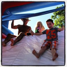 Look out below. Rep. Doug Cox slides down the slide with his granddaughter Tiffany and Kyler Flud during the 2016 GRDA/GLA Grand Lake Legislative Get-A-Way. - Kaylea M. Hutson-Miller / Grove Sun