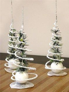 DIY tabletop Christmas trees made with white styrofoam base, greenery for the tree and pipe cleaners spiraling around greenery to give the tree its shape. Love the silver pipe cleaner in the center as the topper and tree trunk. Looks simple enough.  Need to try this one this year.