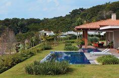 A piscina ladeia o terraço da casa, com estrutura de cumaru e telhas de barro capa e canal.