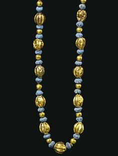 A GREEK GOLD AND FAIENCE NECKLACE  HELLENISTIC PERIOD, CIRCA 2ND CENURY B.C.  Composed of spherical and globular gold beads, some fluted, the larger beads with a ring of beaded wire at the suspension hole, interspersed with ridged blue faience beads; strung with a modern clasp
