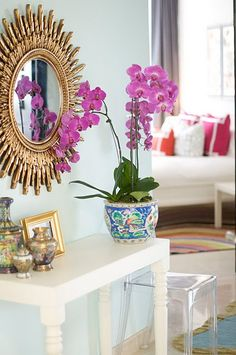 entry way, sunburst mirror, console table, acrylic bench, orchids