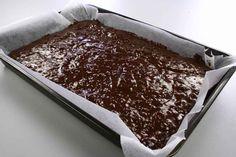 Smelt smørret med chokoladen i en gryde og lad den køle af. Pisk æg og sukker til en luftig æggesnaps. Bland mel, kakao og hakkede valnødder og vend det i æggesnapsen. <BR> <BR> Hæld deje
