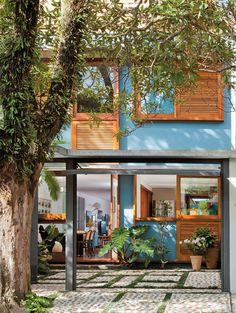 Esta casa geminada passou por uma reforma radical. Com fachadas atualizadas, ambientes redistribuídos e revestimentos novos, ela ganhou muita luz, ventilação e uma cobertura arborizada.
