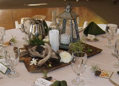 slate and driftwood centerpieces - wine bottle has table number on paper in it