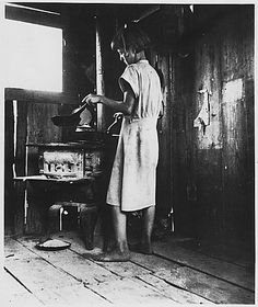 """Great Depression Era: A Girl Making Supper. Farm Security Administration: """"Suppertime"""" for the westward migration. Circa 1936. Picture from the Franklin D. Roosevelt Library, courtesy of the National Archives and Records Administration."""