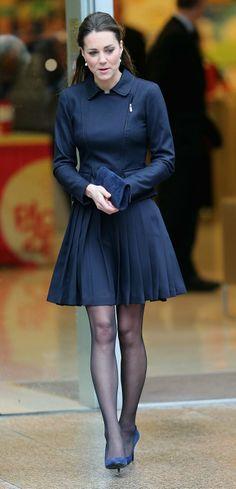 Kate Middleton in a navy pleated dress. É impressão minha ou a meia-calça dela é…