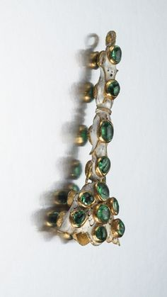 "Some ""mystery jewels"" were also found in the Cheapside Hoard. This gold piece with white enamel and Colombian emeralds is thought to be a fan holder. Large feathers for a fan could be attached on the flared side, and the holder could be attached to a chain on the other end. Courtesy of the Museum of London;"
