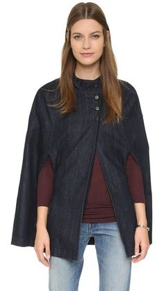 A mock neckline and button closures detail this denim cape that's perfect for fall.   3x1 Denim Cape