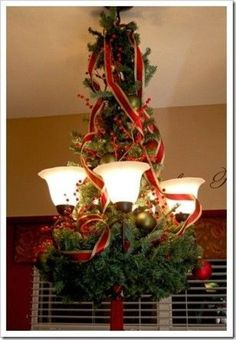Christmas Chandelier Makeover. Wire a greenery wreath to the bottom of the chandelier, then wiring greenery�from the top of the chandelier�chain to�the middle of the chandelier...�Next attaching ornaments at random spacing, adding berries and some wir