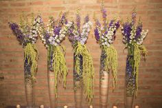 Purple and Green Placecard Table Flowers. Tall delphinium and larkspur tower over their submerged counterparts, with hanging green amaranthus for drama. Loft style. Designed by Laura Daluga CFD of the Anna Held Floral Studio in Chicago.