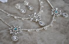 This elegant three piece set includes a headpiece with coordinating necklace and pin back earrings.  A truly unique and stunning combination of accessories.  It can be made with tiffany blue crystals incorporated into the headpiece design to act as the bride's ʺsomething blueʺ item or be made with all clear crystals.