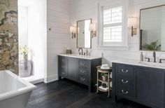 Transitional master bathroom features separate black washstands adorned with gold pulls topped with contrasting white quartz placed below gold mirrors flanking a round gold etagere facing a rectangular freestanding tub atop dark floors.