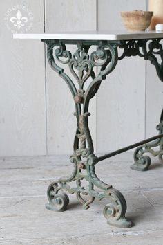 Stunning antique cafe table from France with the most gorgeous iron base and carerra marble top. Intricate scrolling details drip along the hunter green frame, adding such a parisian flair. So chic and wonderful, a fantastic place to enjoy a cup of tea with a friend, or would make a great side table as well.  28H x 39W x 18D  Circa: 1900  Return Policy: This item is not eligible for returns or exchanges so please make sure to look over the pictures and ask ...