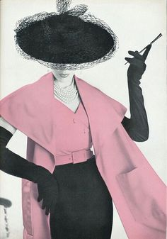 Pink & black vintage woman in hat, gloves, wrap smoking cigarette.