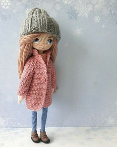 Amigurumi doll in a pink coat with a grey knitted hat.