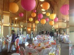 Add a pop of color with hanging lights and chair sashes at any wedding reception