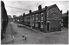 Grim: Three boys play with guns along cobbled streets between rows of back-to-back terraced houses in Leeds in July 1970. The title of the exhibition - Make Life Worth Living - apparently takes inspiration from the Beechams Pills advertisement painted on the brick wall
