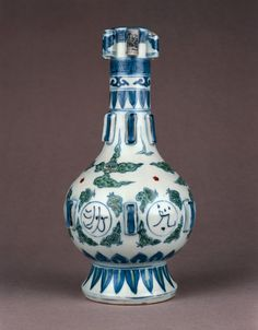 Porcelain vase in form of ancient bronze. Six vertical tubes below rim, six low relief rectangles around base of neck and six rectangular cubes around waist. Doucai-style decoration with underglaze blue outlines and overglaze red and green enamels. Six roundels around body with pseudo-Arabic script with ruyi and cloud motifs. Lotus leaves and petals around neck and foot. Base unglazed. Ming dynasty Wanli period. The British Museum.