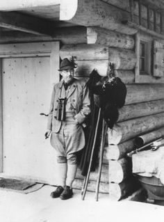 Heinrich Himmler poses in front of a hunting lodge, while wearing traditional Bavarian hunting clothes.