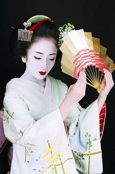 """Makiko poses with a fan, and you can just make out the crest of the Inoue School in the center of the fan. Of her artistic training in dance and music, Makiko says, """"I was once told it does not matter whether I am good or bad. What is important is the spirit of wanting to learn."""""""