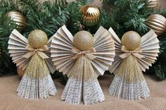 Our ever-popular Book Angels are now available in ornament form! For your consideration is this lovely set of 3 Book Angel Christmas ornaments in gold. Each one measures approximately 5 inches tall and about 3 inches wide. We have taken a discarded book, cut it down to size and folded its pages by hand to create the base of each angel. The folds are then glittered in gold ultrafine glitter. The heads are made with shatter-proof ornaments and glittered gold as well. A cute little gold bow…