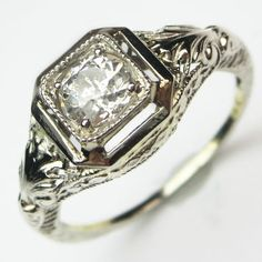 Acanthus Leaf: Classical scrolling foliage adorns each shoulder of this elaborately detailed ring. Ca.1930. Maloys.com