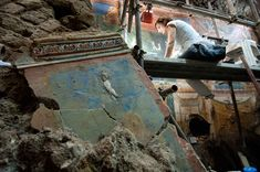 An archaeologist perches on scaffolding in the triclinium. Some of the room's walls are preserved to their full height of nearly 18 feet, while others were toppled, likely by the force of the eruption of Vesuvius almost 40 miles away.