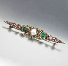 One side bears ruby gemstones and the other garnet gems with the center a natural white pearl in this late Victorian Austro Hungarian brooch circa 1890.