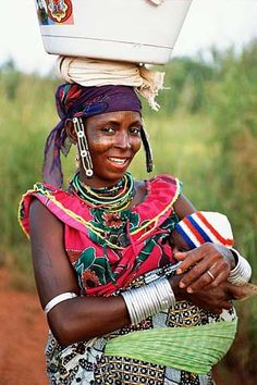 A Beninois woman returns from getting water with her baby