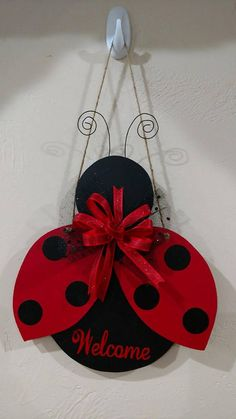 Handpainted, wooden ladybug. Embellished with black and red vinyl, wire antennas, and a red ribbon/black tulle bow.