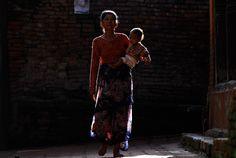 Nepálska žena s dieťaťom kráča ulicou Bhaktapuru na predmestí Káthmandu. (AP Photo/Niranjan Shrestha)
