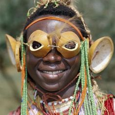 An Mtaita musician. His 'glasses' are made from the tips of calabashes. His ear ornaments are also made of calabashes or gourds. Coast Province, Kenya.