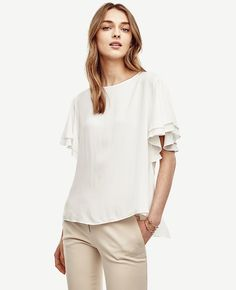 """Flutter sleeves add breezy femininity to this double-layered crepe top, finished with a pretty back peplum detail. Jewel neck. Flutter sleeves. Back keyhole with button closure. Back peplum. 23 1/2"""" long."""
