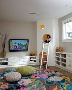 Kids playroom, large floral area rug, knit poufs, custom kids play house with white ladder.