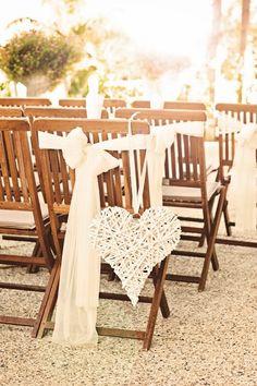 Židle dekorované krémovými mašlemi a proutěnými srdci.