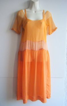 peach crepe silk two piece 20s dress. underdress is matching peach on the top part with shoulder straps separated from the sleeves followed by a pink sash and a mandarin orange skirt. sleeves have a ruffled finish with metal filigree edging. underdress snaps up the side in back with