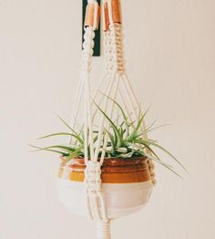 Hang up this handcrafted macramé hanger to spruce up the space with some greenery. The hand-knotted hanger gently nests a pot or bowl, to fill with a well-tended bit of green or even fresh produce. Copper accents add rosy shine, contrasting with the neutral colored cord.