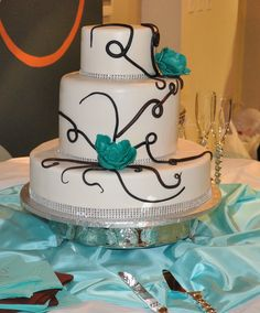 Unique three tier wedding cake with turquoise flower accents. #weddingcake