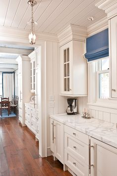 white cabinets, white marble, wood floors