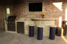 Outdoor kitchen with stainless BBQ and refrigerator, stone bar with built in mosaic covered stools. By Outdoor Signature in Argyle, TX