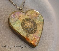 This heart necklace is pastel and antique gold with a swirl charm to have the appearance of an open locket.  Sheets of liquid polymer clay were cured with paint, ink, metal leaf, and glitter to form a dimensional veneer. MEMBER - Kathryn Designs