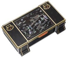 A RARE ART DECO LACQUER AND GEM-SET CIGARETTE BOX, BY CARTIER  Of rectangular outline, the lid with central lacquer and dyed mother-of-pearl plaque depicting a Chinese nocturnal scene with cabochon and calibré-cut sapphires representing the moon and its reflection in the water, set between two faux tortoiseshell panels with scroll motifs decorated with coral, to the coral clasp and stepped ebony base, opening to reveal two wooden compartments, circa 1925