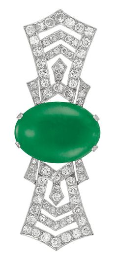 Art Deco Jade and Diamond Brooch   Platinum, the openwork stylized bow brooch centering one oval cabochon jade* approximately 19.5 x 14.45 x 4.05 mm., flanked by tapered ribbons set throughout with 74 old European-cut and single-cut diamonds approximately 1.90 cts., circa 1920