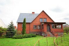 Отделка кирпичного загородного дома оранжевого цвета в деревенском стиле с рустами