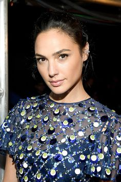 Backstage at the 2017 MTV Video Music Awards, Gal stunned in a sequin dress, pulled back hair and bling earrings.