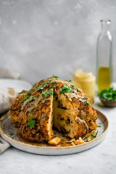 Whole Roasted Cauliflower with Tahini Sauce: tender, flavor-packed roasted cauliflower head with olive oil, generous spices, and a delicious tahini sauce. Roasted Cauliflower Head, Cauliflower Dishes, Vegan Cauliflower, Tahini Recipe, Tahini Sauce, Veggie Recipes, Vegetarian Recipes, Cooking Recipes, Thanksgiving Recipes