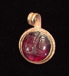 A ROMAN GOLD PENDANT, ca. 1st-3rd century AD. Circular in form set with a carved garnet intaglio.