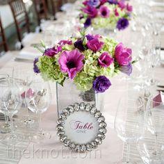 Arrangements of purple lisianthus, pale-green hydrangeas and magenta anemones filled cracked-mirror planters.